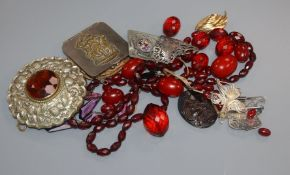 Assorted items including simulated amber necklaces and a silver belt buckle.
