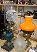 Three oil lamps, two with shades and a spare matching shade tallest 60cm