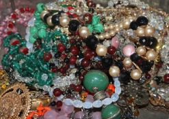 A box of assorted costume jewellery, including necklaces.