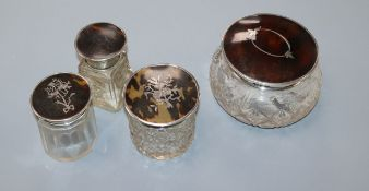 Three assorted silver and tortoiseshell pique mounted glass toilet jars and a similar salts bottle.