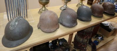 Seven various WWI and WWII helmets