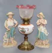 A pair of French coloured biscuit figures and an oil lamp