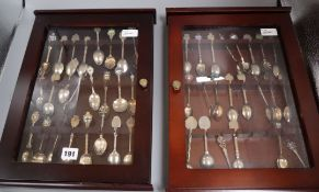 A collection of 48 souvenir spoons, plated, enamelled, etc. in two glazed display cases