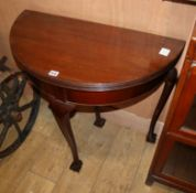 A mahogany Georgian style demi lune card table with ball and claw feet W.76cm