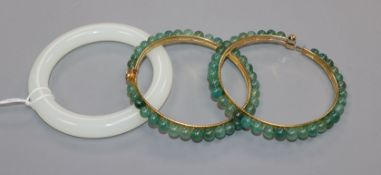 A Chinese white jade bangle and two green stone bangles