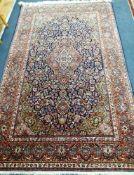 A Kashan red ground rug 212 x 130cm