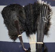 A black and white ostrich feather fan and two black ostrich feather fans, the former with silver