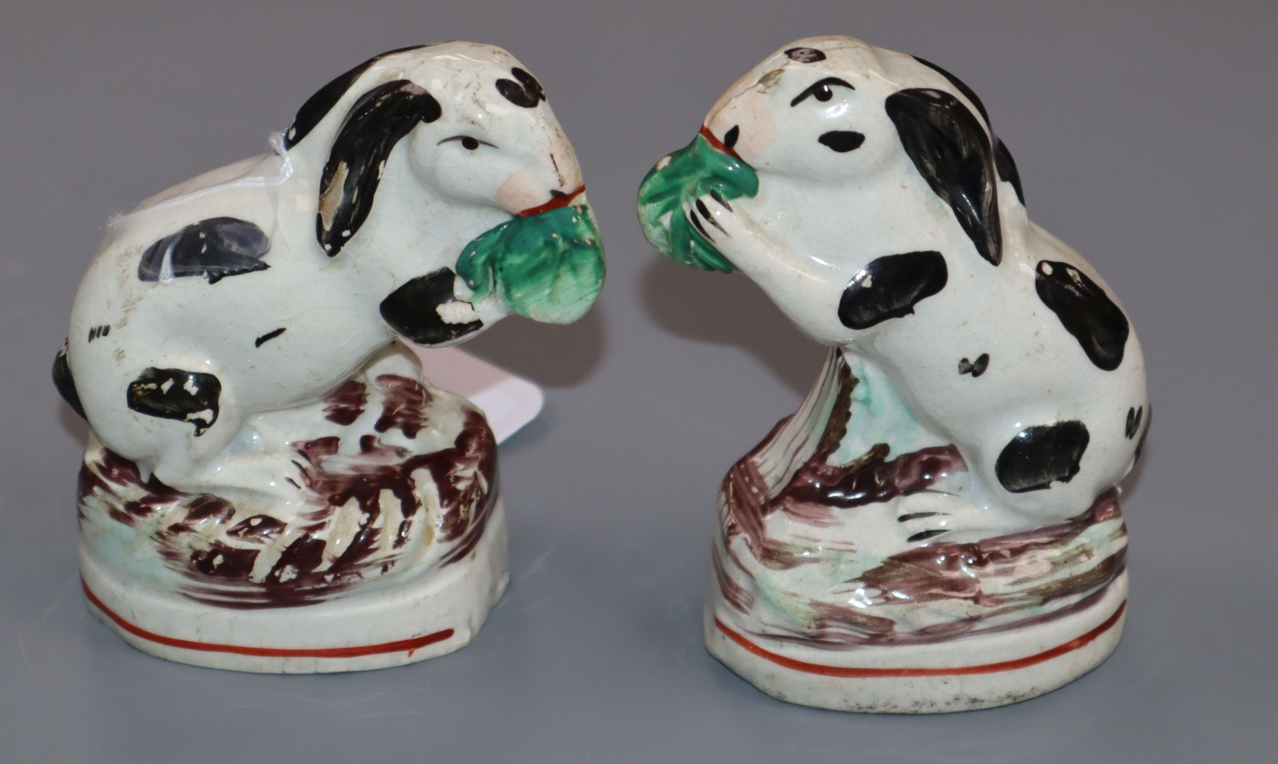 Lot 279 - A pair of Staffordshire black and white pottery rabbits, seated on their haunches and nibbling