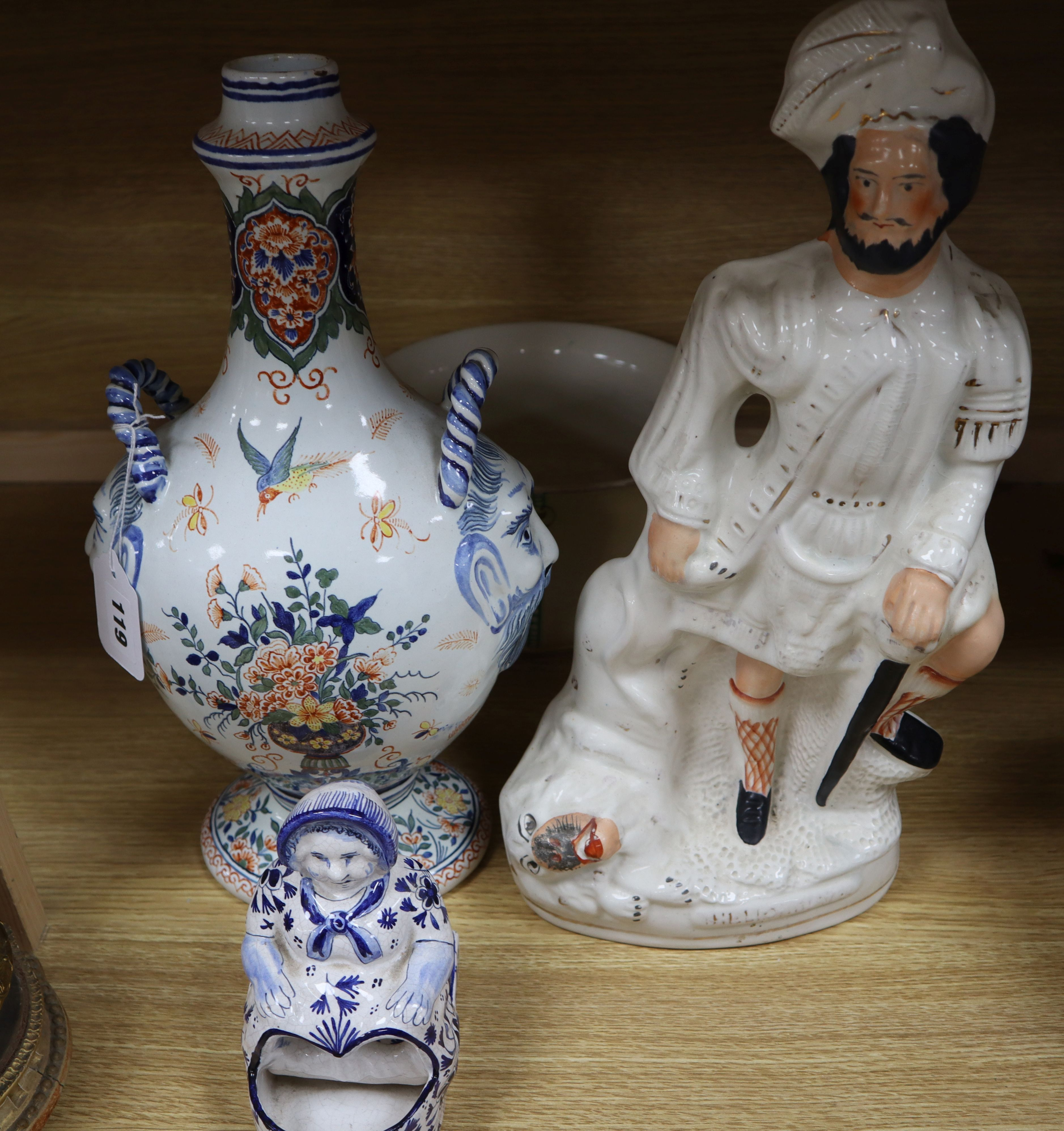 Lot 137 - A French faience pilgrim flask, a delft figure, a Staffordshire figure and Victorian chamberpot