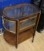 A two-tier drinks trolley of oval form, with glazed upper section and galleried undertier W.72cm