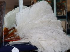 Two white ostrich feather fans, one with gold-monogrammed blond faux-tortoiseshell guard sticks
