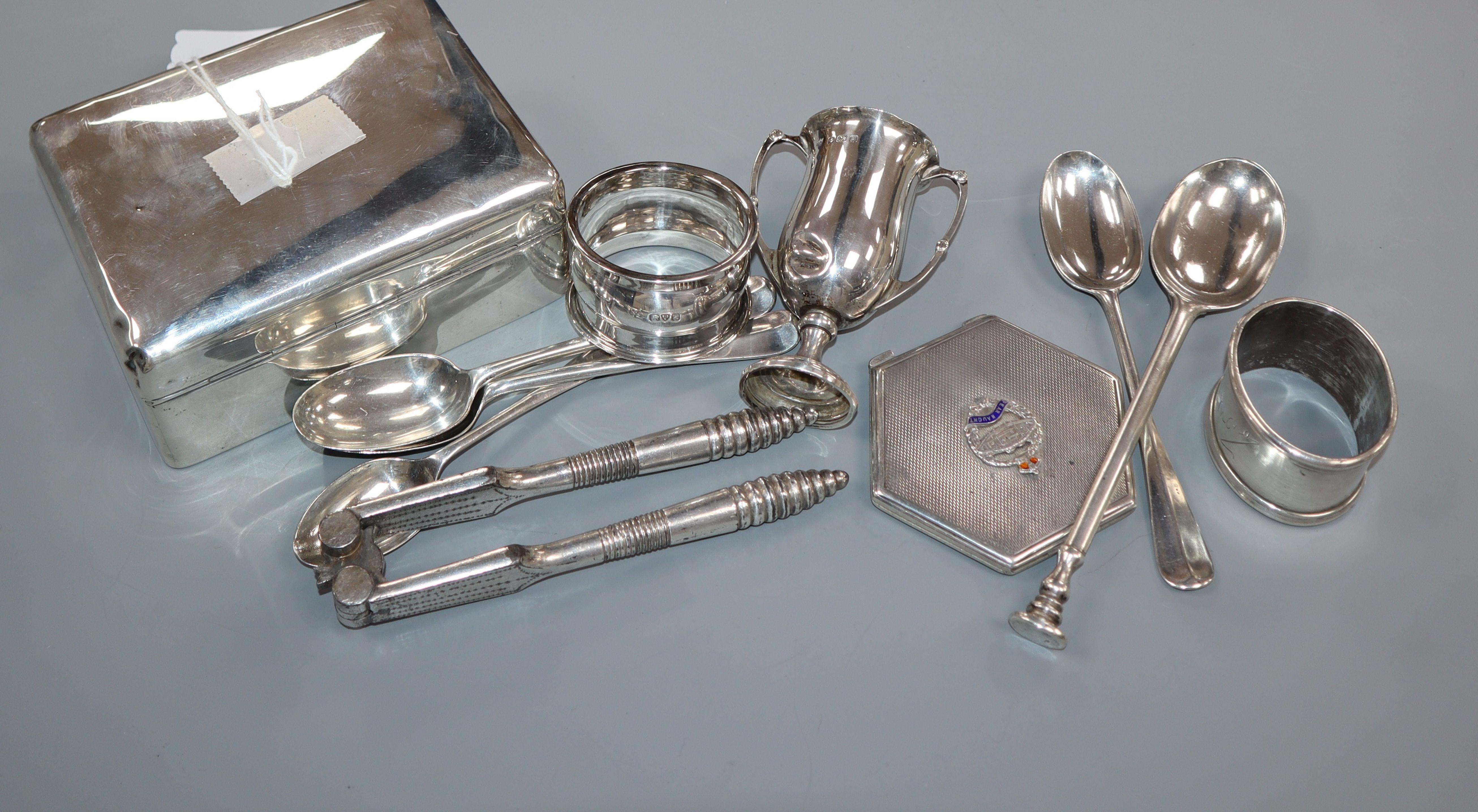 Lot 669 - A silver cigarette box, silver pencil, two silver napkin rings, small silver trophy cup, five silver