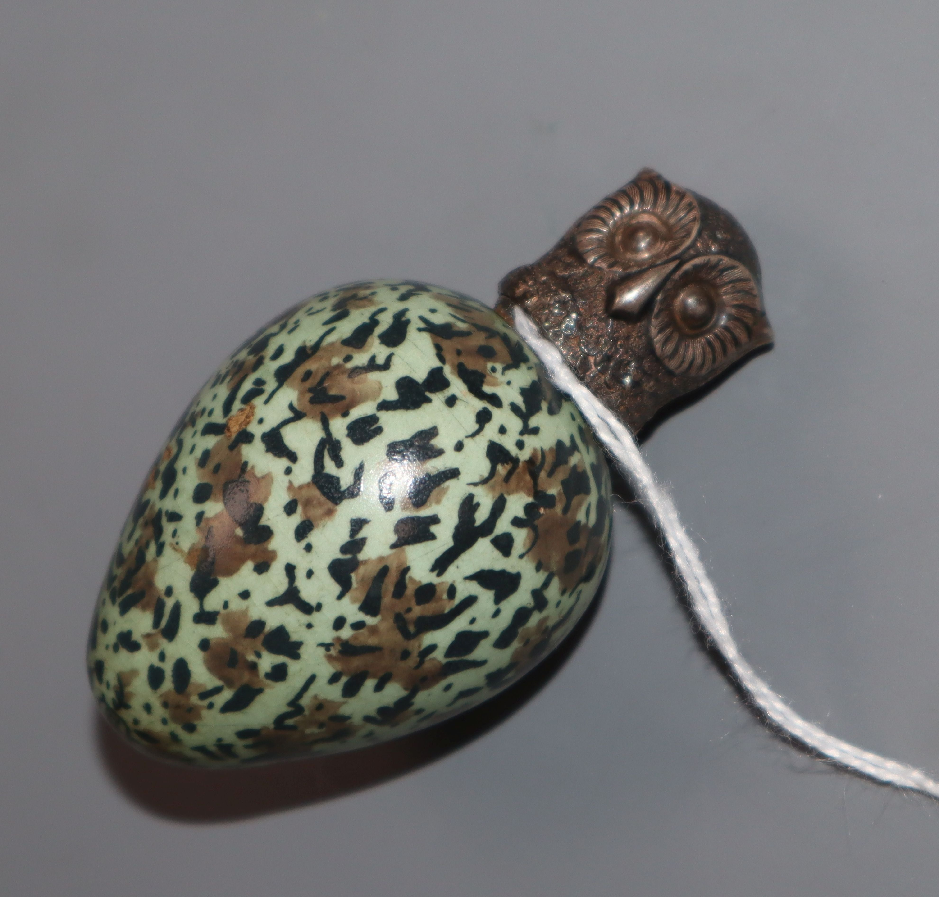 Lot 272 - A Victorian novelty ceramic scent flask in the form of an egg with screw-on white metal top modelled