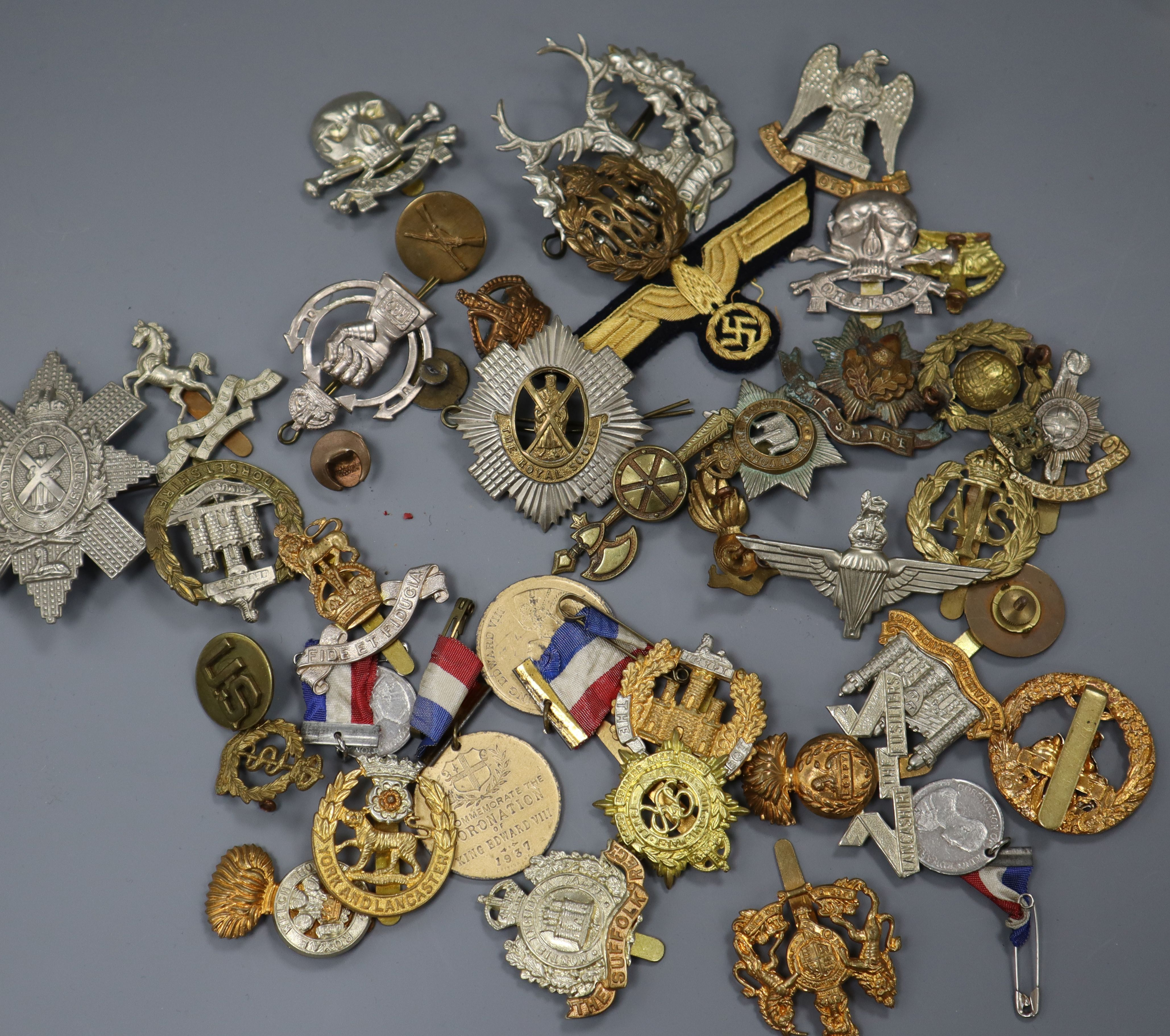 Lot 320 - A collection of military cap badges etc.