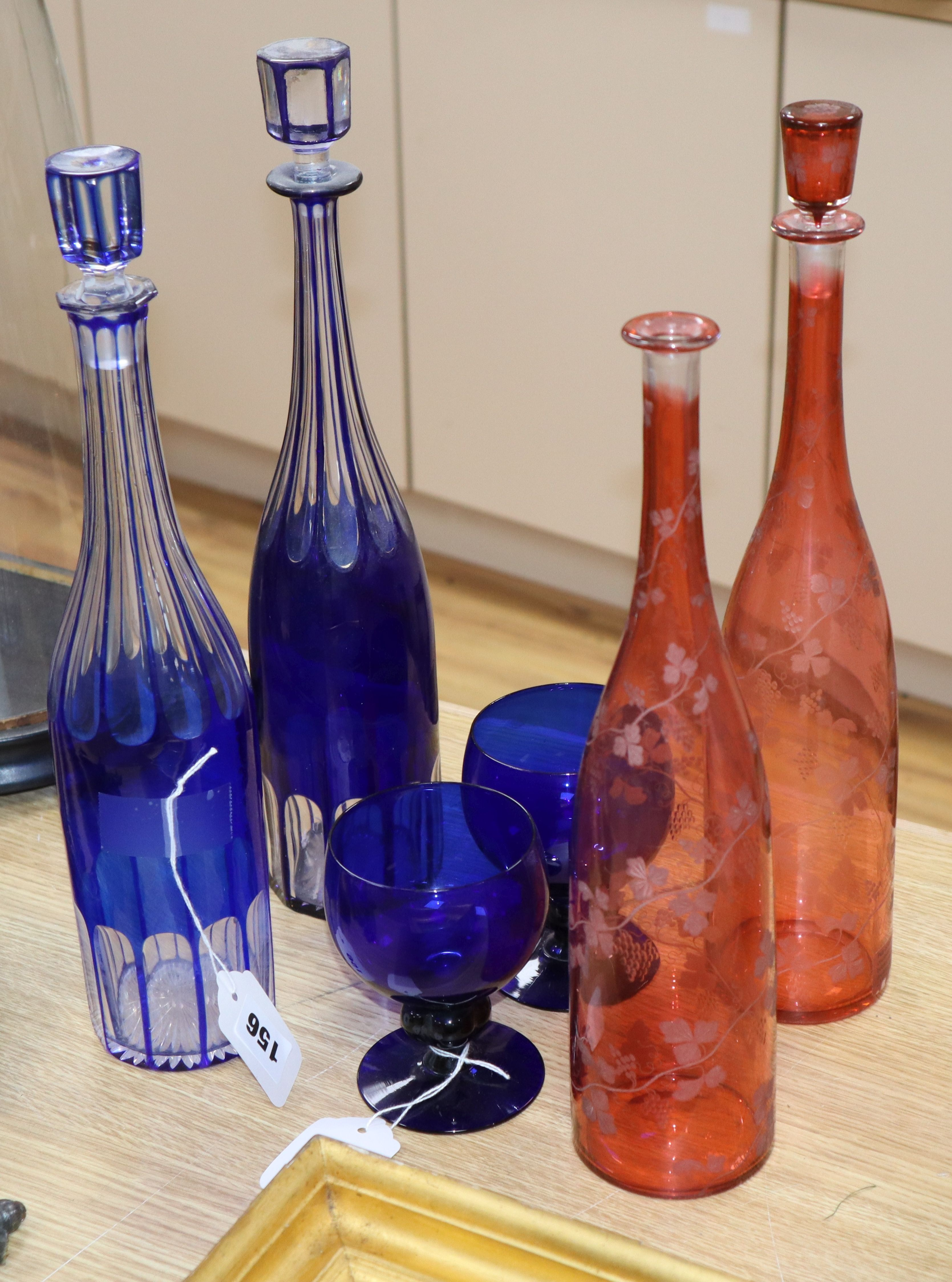 Lot 156 - Two blue overlay glass decanters and stoppers, two ruby flask glass decanters and a pair of blue