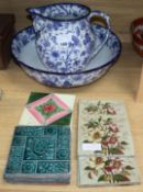 Thirteen Victorian and later pottery tiles, a jug and a basin