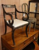A Regency style ebonised painted elbow chair and a French lyre back cane seat side chair