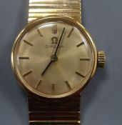 A lady's 9ct gold Omega manual wind wrist watch, on a 9ct gold Omega strap.