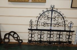 A 17th century wrought iron wall sconce, an iron guard and a wrought iron roasting hanger