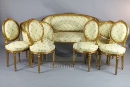An early 20th century Louis XVI style carved and giltwood seven piece salon suite, comprising a