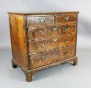 A George III featherbanded walnut chest of two short and three graduated long drawers, on bracket
