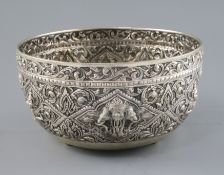 An early 20th century Thai silver bowl, embossed with deities amid scrolling foliage, on three