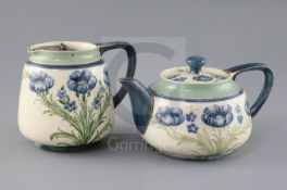 A Moorcroft Macintyre 'blue poppy' teapot and matching milk jug, Rd. no. for 1905, decorated with
