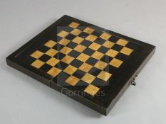 An early 19th century ebony and boxwood travelling games box, with external chess board and internal