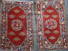 A near pair of Tibetan red ground rugs, woven with central medallions, spandrels and peony meander