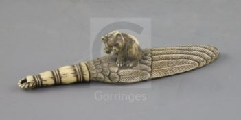 A good Japanese ivory paper knife, Meiji period, carved as a kitten seated upon a giant falcon