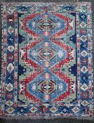 A Caucasian Kazak red and blue ground rug, with three central medallions in a field of hooked motifs