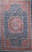 A Tabriz carpet, with central medallion in a field of scrolling foliage, with three row border, 12ft