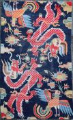 A Tibetan 'dragon' rug, woven with two confronting dragons, cockerels and stylised foliage, c.
