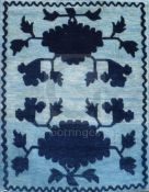 A Tibetan saddle seat rug, woven with black stylised peonies, in silhouette, against a silver field,