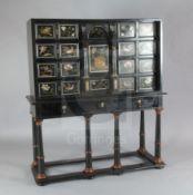 A 17th/18th century Italian and later pietra dura and ebony veneered cabinet on an ebonised wood