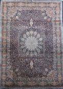 A Kashmir blue ground silk on cotton carpet, with central flower head motif in a field