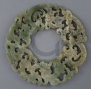A Chinese archaistic celadon jade disc, carved and pierced with interlaced chilong, D. 23.2cm