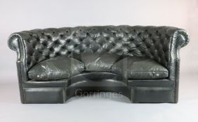 A buttoned black leather concave settee, with triple squab cushions and brass studding, W.7ft D.