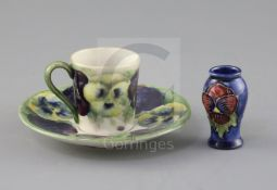 A Moorcroft 'pansy' pattern coffee cup and saucer, c.1915 and a similar later miniature vase, the