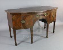 A George III mahogany bowfront sideboard with central drawer flanked by a cupboard and deep