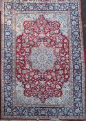 A Kirman red ground carpet, with central foliate medallion in a field of scrolling foliage, with