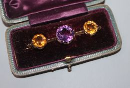 An early 20th century yellow metal, amethyst and citrine three stone bar brooch, 52mm.