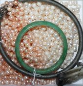 Two cultured pearl opera length necklaces (white and champagne), a green jade bangle and a jade