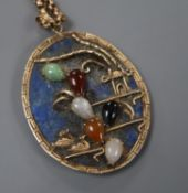 A yellow metal and multi gem set mounted lapis lazuli set oval pendant, on an early 20th century