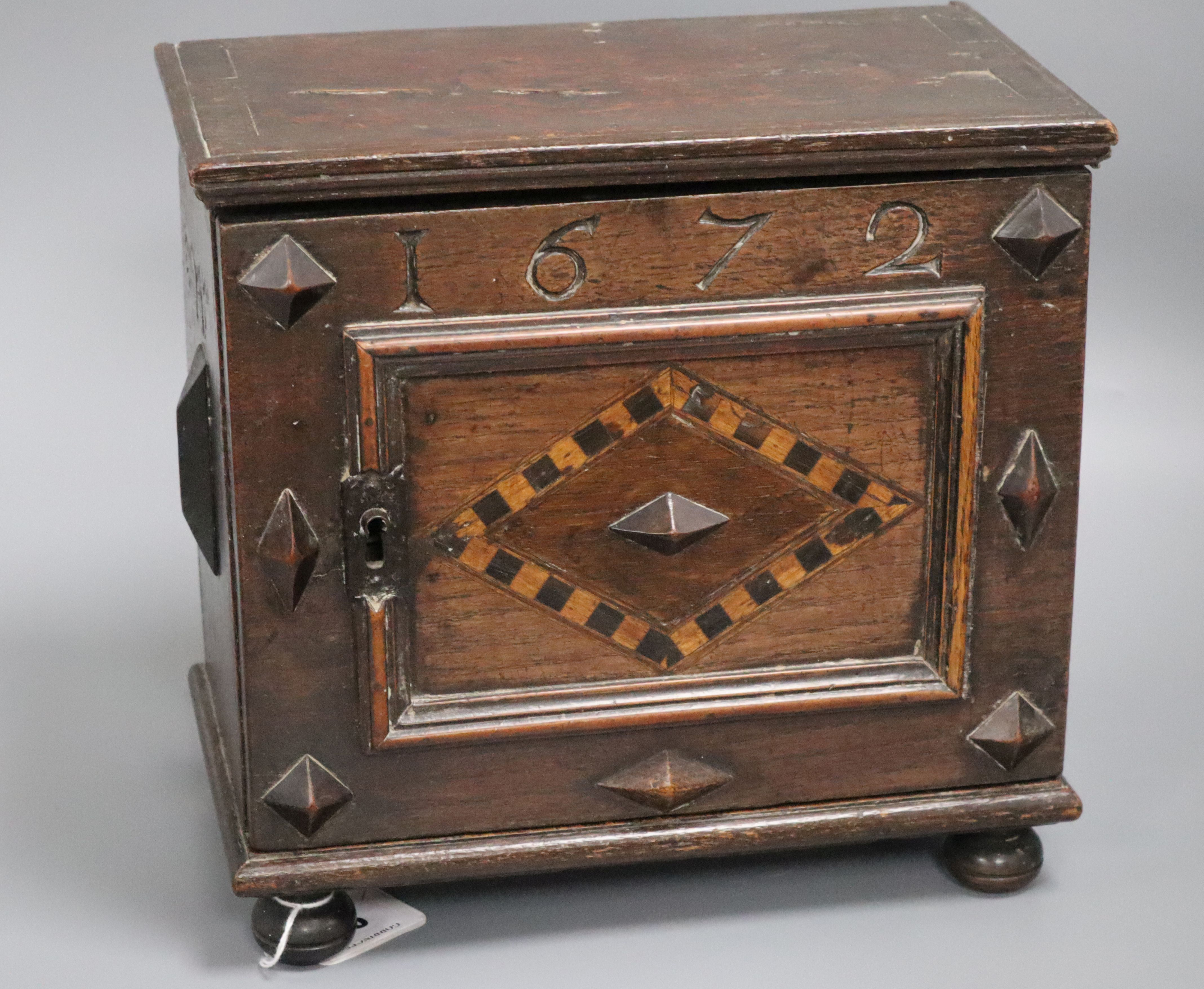 Lot 46 - An inlaid oak spice cabinet, carved with the date, 1672 W.29cm