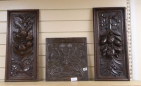 A 19th century carved oak panel and two later oak panels