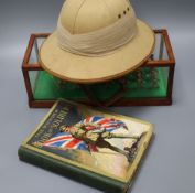 A cased cast lead marching soldier's pith helmet and The Wonder Book of Soldiers