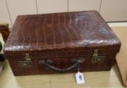 An early 20th century crocodile skin toilet case