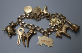 A 1960's 9ct gold charm bracelet, hung with ten assorted charms, gross 26 grams.