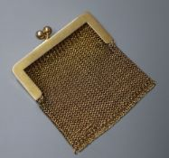 A small 14k yellow metal mesh purse.